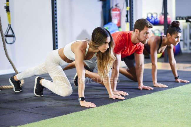 Jóvenes ejercitando variaciones de tablón en un gimnasio - foto de stock