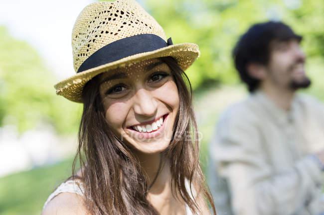 Портрет щасливого молодої жінки в парку зі своїм хлопцем у фоновому режимі — стокове фото