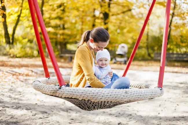 Счастливая девочка отдыхает с мамой на качелях осенью — стоковое фото