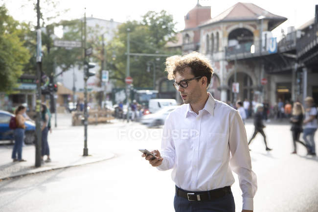 Germany, Berlin, businessman looking at cell phone outdoors — Stock Photo