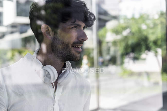 Portrait of young man wearing headphones and looking away — Stock Photo