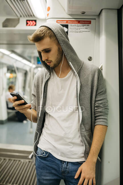 Young man using smartphone in metro — Stock Photo