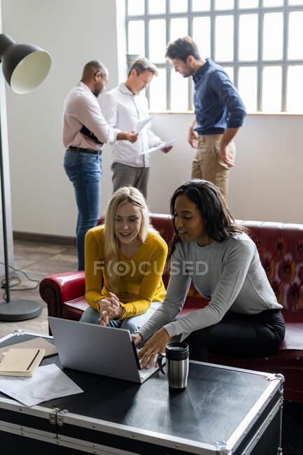 Geschäftsteam nutzt Laptop und diskutiert Dokumente im Loft-Office — Stockfoto