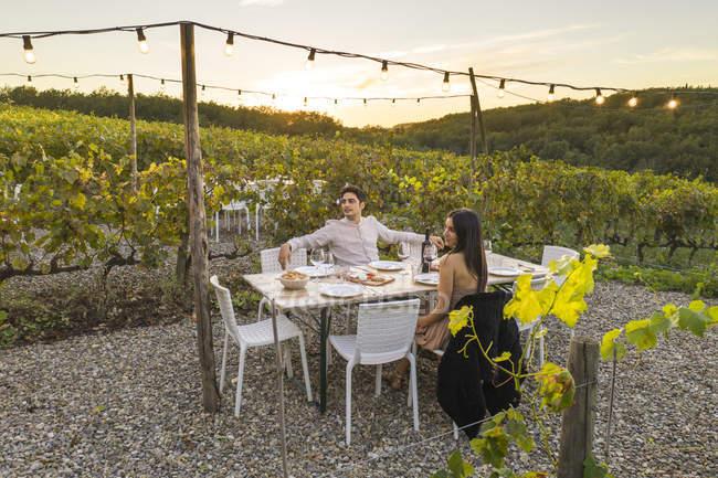 Italy, Toscânia, Siena, pares novos que têm o jantar em um vinhedo — Fotografia de Stock