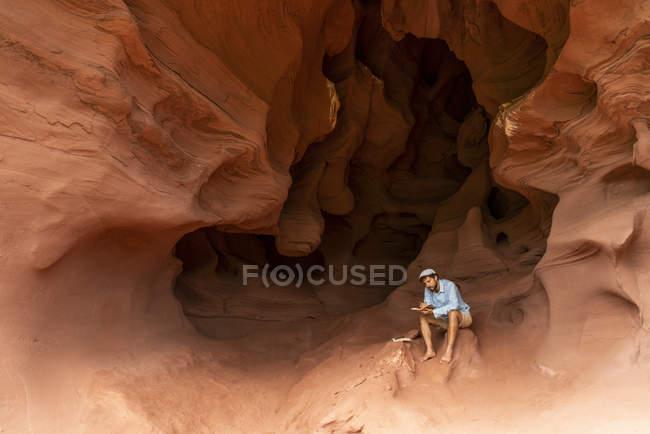Jovem sentado em uma caverna, tomando notas — Fotografia de Stock