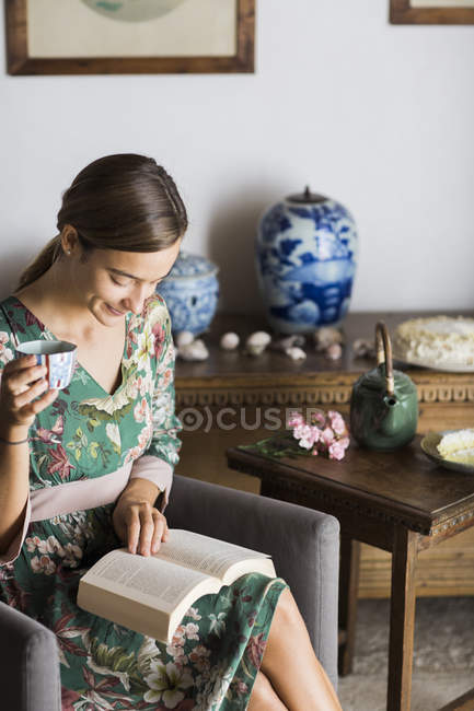 Young woman drinking cup of tea while reading a book at home — Stock Photo