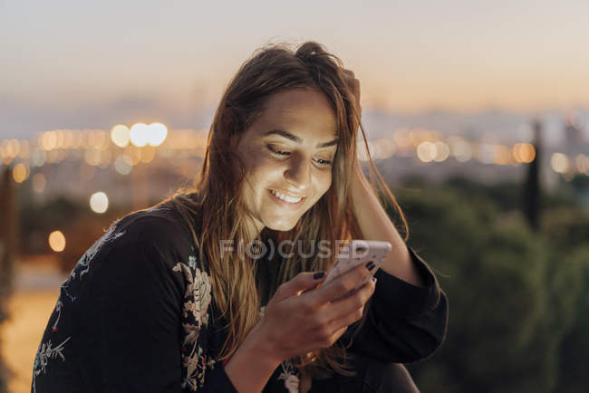 Spain, Barcelona, Montjuic, smiling young woman at dusk using cell phone — Stock Photo