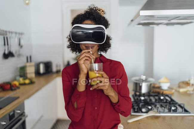 Woman standing in her kitchen, wearing VR goggles, drinking orange juice — Foto stock