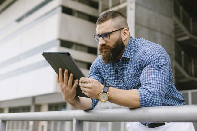 Бородатый хипстер ский бизнесмен в очках, наручных часах и клетчатой рубашке с помощью цифрового планшета — стоковое фото