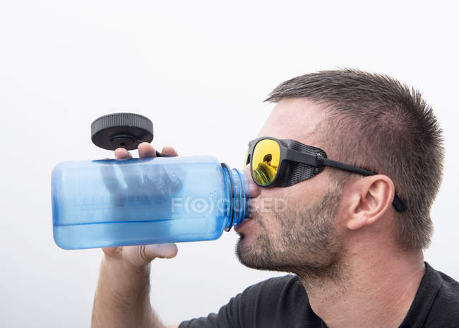 Athlete with snow goggles drinking water — Stock Photo