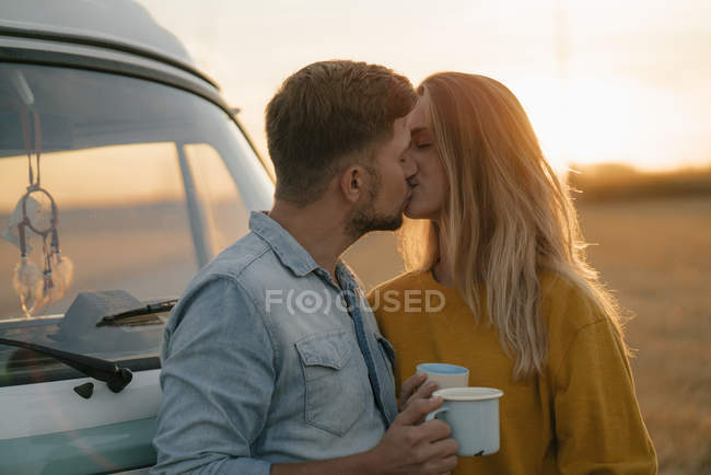 Молодая пара целуется в фургоне в сельской местности — стоковое фото