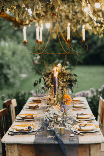 Festive laid table with candles outdoors — Stock Photo