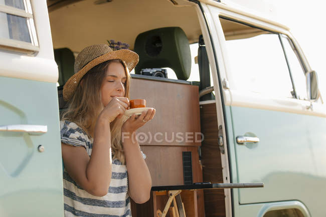 Young woman enjoying a cup of coffee in camper van — стокове фото