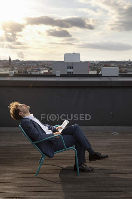 Germany, Berlin, businessman relaxing on roof terrace at sunset — Stock Photo
