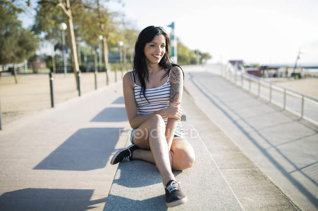 Smiling tattooed young woman relaxing on bench — Stock Photo
