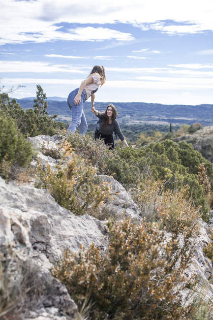 Spain, Alquezar, young woman on a hiking trip giving a helping hand for a friend — Stock Photo