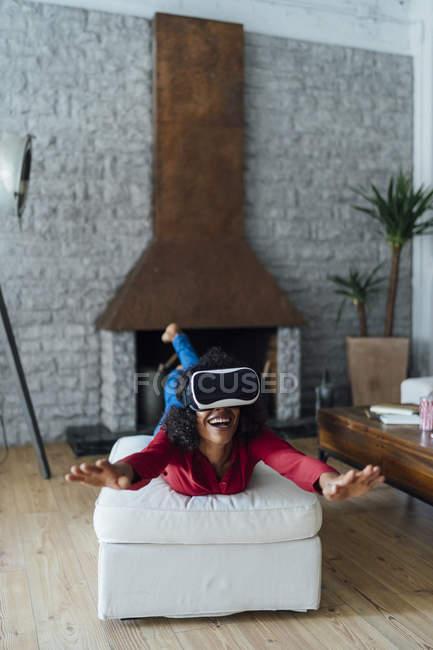 Женщина лежала на мебели, носила защитные очки, притворялась, что летает — стоковое фото