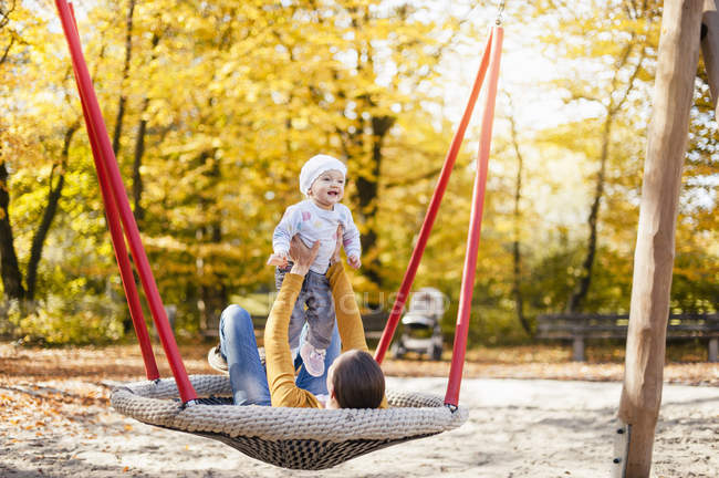 Happy baby girl relaxing with her mother on a swing in autumn — Stock Photo