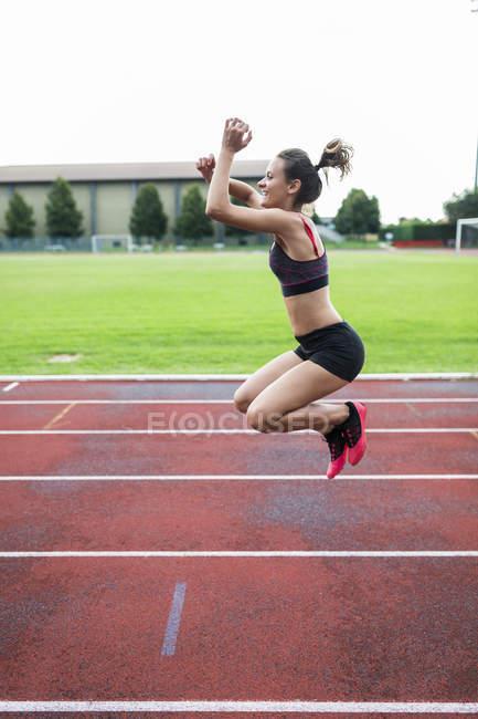 Юный бегун, прыгающий от радости на ипподроме — стоковое фото