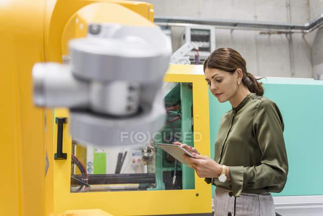 Geschäftsfrau überprüft Industrieroboter in Hightech-Firma — Stockfoto