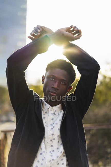 Молодой человек, поднимая руки со скрещенными запястьями — стоковое фото