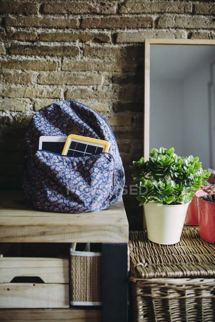 Chargeur panneau solaire et une tablette dans un sac à dos à la maison — Photo de stock