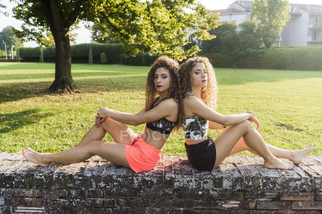 Портрет сестер-близнецов, сидящих босиком спиной к спине на стене летом — стоковое фото