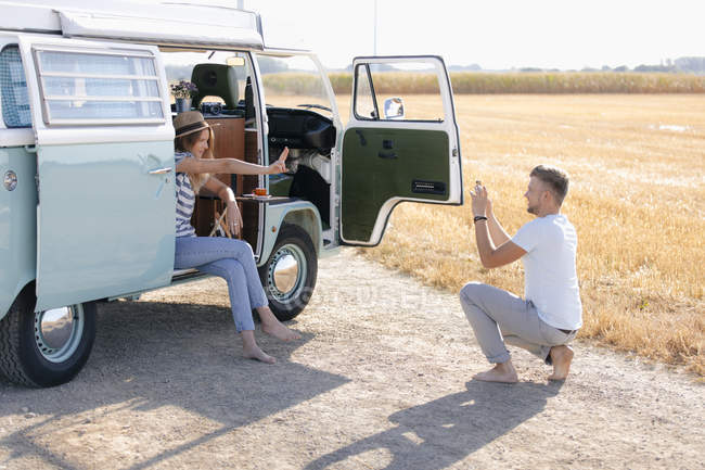 Young man taking cell phone picture of girlfriend inside camper van in rural landscape — стокове фото