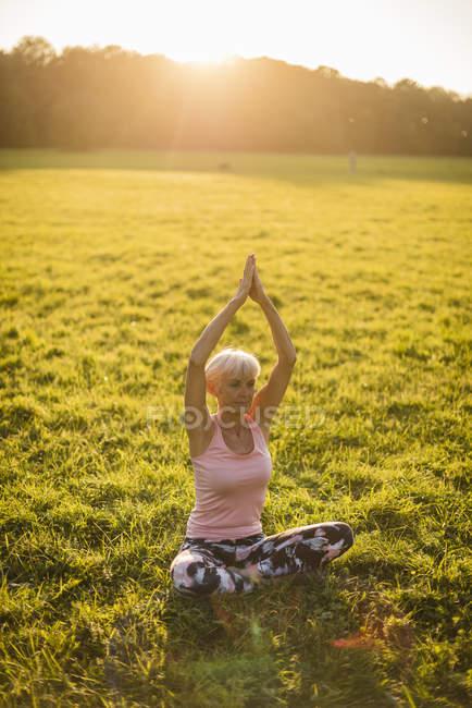 Femme âgée faisant du yoga sur prairie rurale au coucher du soleil — Photo de stock