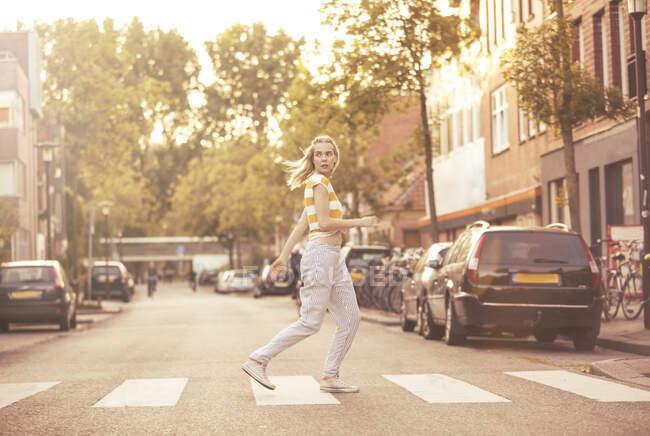 Молодая женщина шла по пешеходному переходу Зебра — стоковое фото