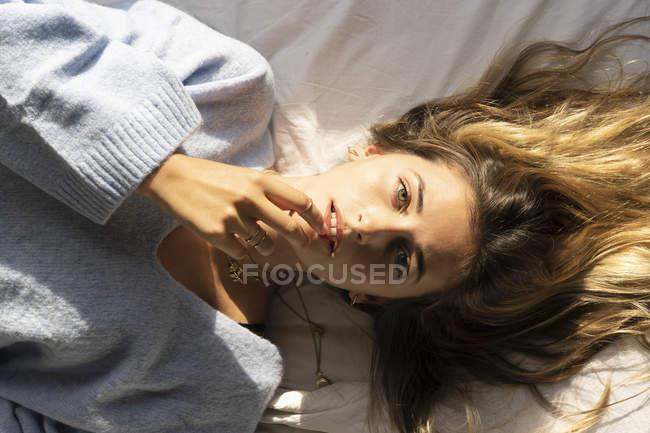 Retrato da mulher nova bonita que encontra-se na cama e que olha a câmera — Fotografia de Stock