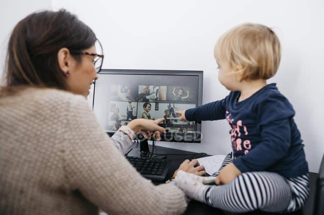 Mãe com a pequena filha sentada na mesa olhando para a tela do computador — Fotografia de Stock