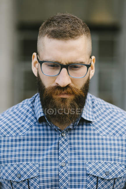 Portrait of bearded hipster businessman wearing glasses and plaid shirt — Stock Photo