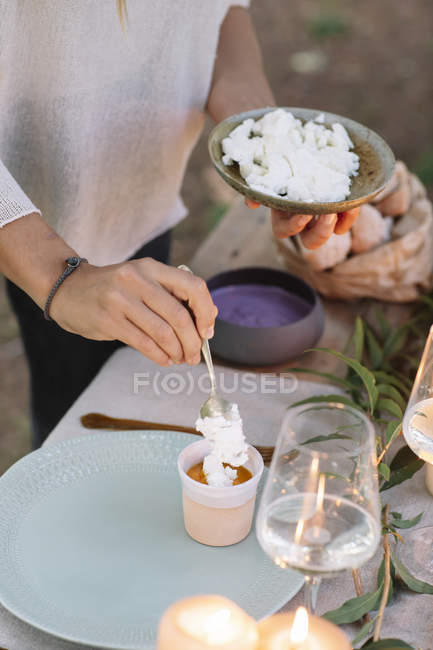 Close-up of woman preparing a romantic candlelight meal outdoors — Stock Photo