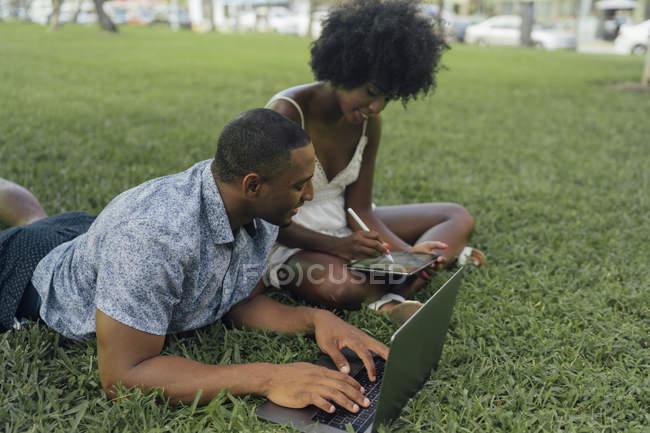 Pareja joven usando tableta y portátil en el césped en un parque - foto de stock