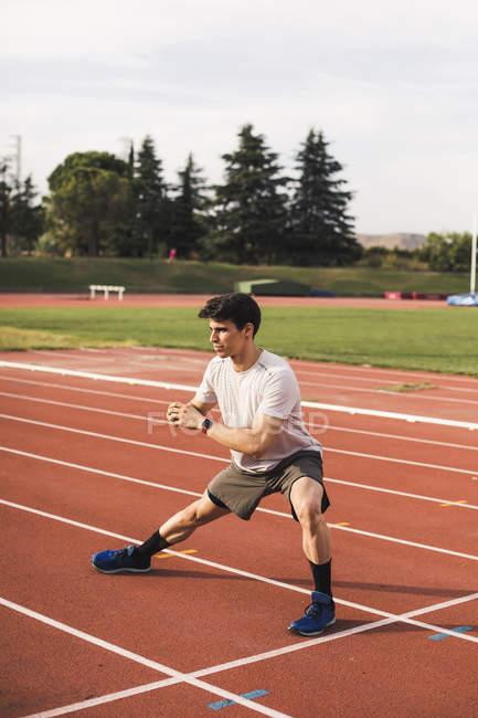 Athlète assis à faire des exercices d'échauffement sur une piste de tartan — Photo de stock