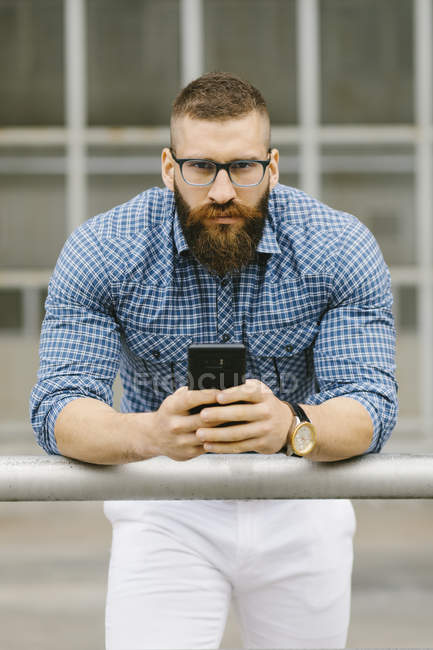 Portrait of bearded hipster businessman with smartphone leaning on railing — Stock Photo