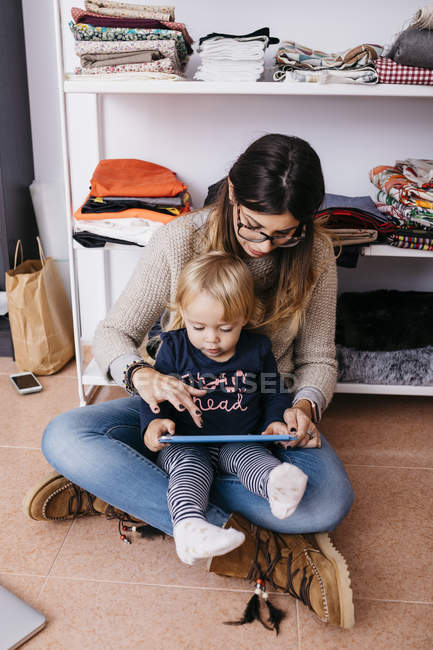 Mother and little daughter sitting on the floor at home using tablet — Stock Photo