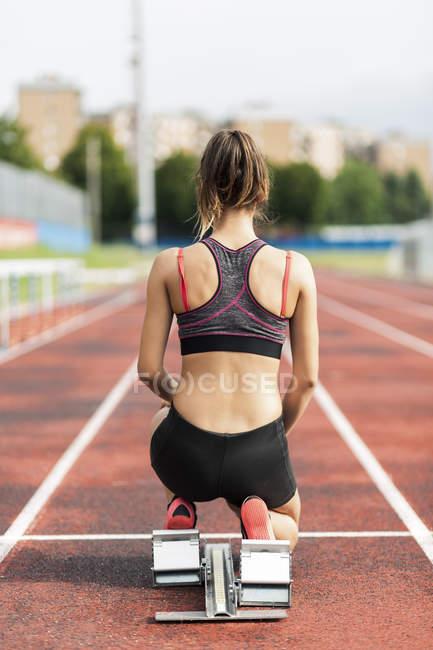 Teenage runner kneeling on starting block — Stock Photo