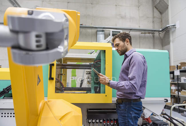 Geschäftsmann überprüft Industrieroboter in Hightech-Firma — Stockfoto