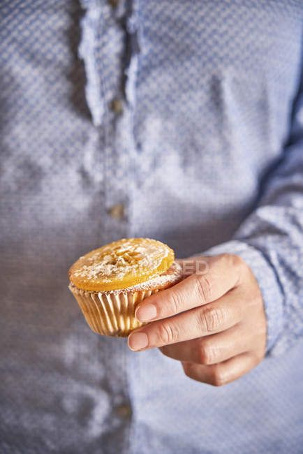 Woman's hand holding muffin with candied orange slice, close-up — стокове фото
