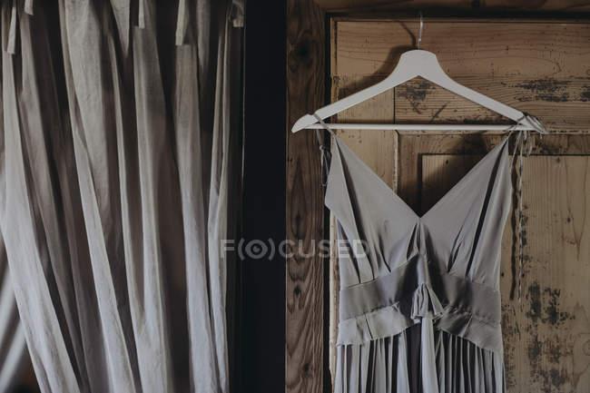 Grey dress hanging at wooden door — Stock Photo