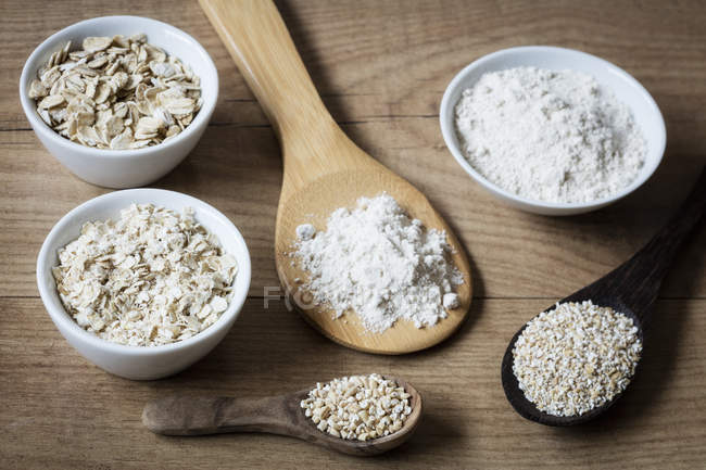 Two variations of oat flakes, oat bran, oatmeal and steel-cut oats — Stock Photo