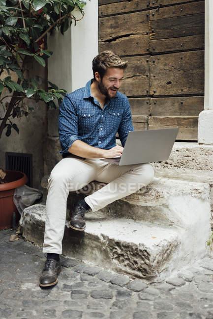 Lachender Geschäftsmann sitzt auf Stufen im Hof und benutzt Laptop — Stockfoto