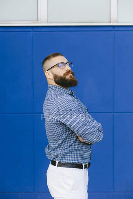 Портрет бородатого хипстера-бизнесмена в клетчатой рубашке и стоящего на синем фоне — стоковое фото