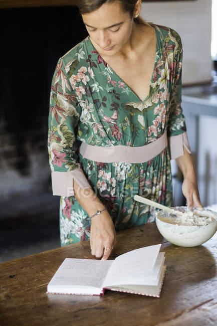 Jeune femme préparant la pâte de gâteau, regardant la recette — Photo de stock
