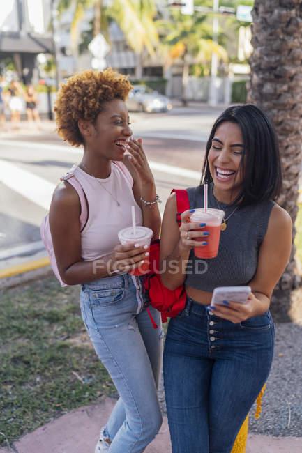 États-Unis, Floride, Miami Beach, deux amies heureuses avec téléphone portable et boisson gazeuse dans la ville — Photo de stock