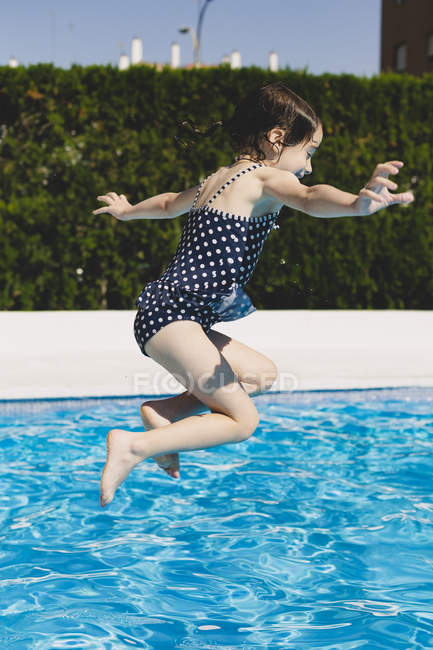 Happy little girl jumping into swimming pool — Stock Photo
