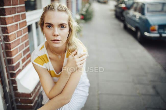Портрет молодой женщины, сидящей перед домом — стоковое фото