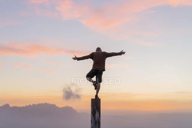 Espanha, Barcelona, Parque Natural de Sant Llorenc, homem de pé no pólo ao pôr do sol — Fotografia de Stock